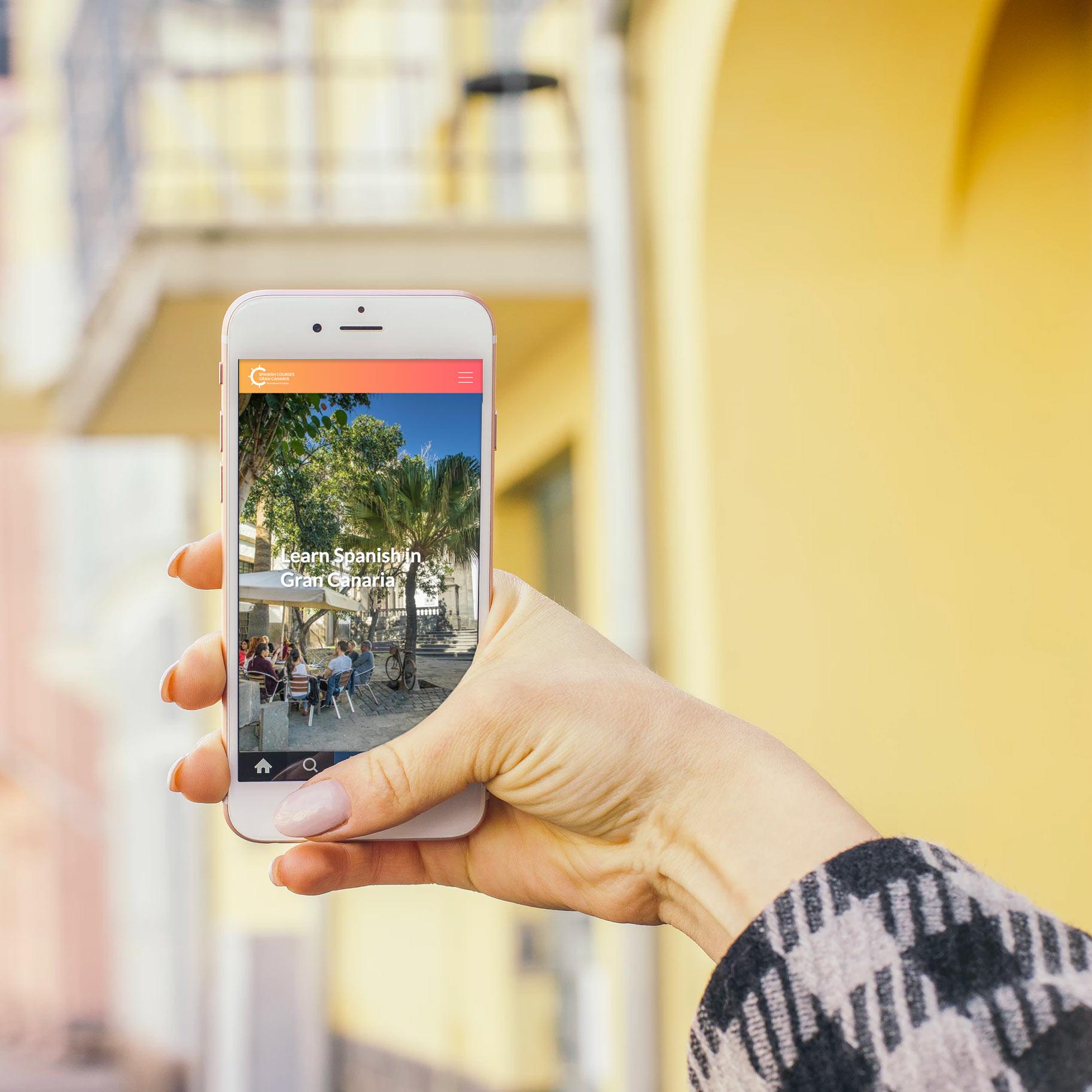 Mano con móvil visitando la web de Spanish Courses Gran Canaria